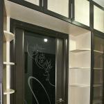 Встроенный библиотечный шкаф имеет радиусные полки вокруг проема двери.